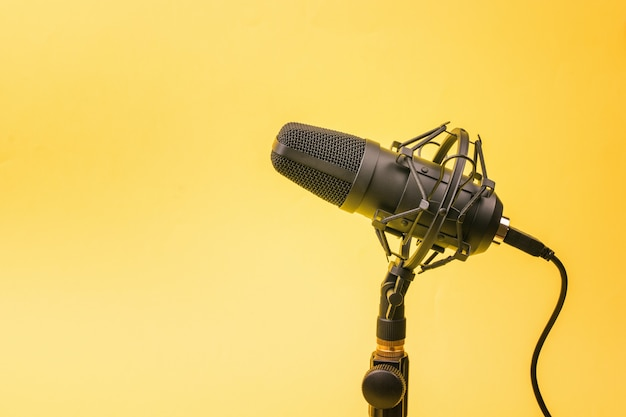 Modern condenser microphone on a stand on a yellow wall