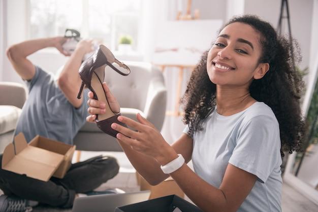 現代の消費主義。彼女の新しい靴を手に持って笑って喜んでポジティブな女性