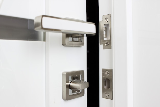 Modern, contemporary satin handle. modern white door with chrome metal handle.