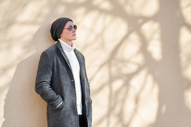 Modern cool hipster trendy man in stylish sunglasses wearing a fashionable gray coat, white sweater and black jeans