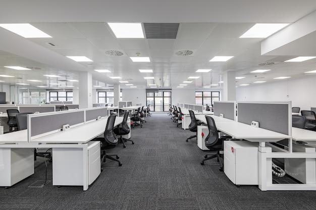 白とグレーの空のオフィスワークステーションのミニマリストモダンなデザインのモダンな企業のオープンオフィス