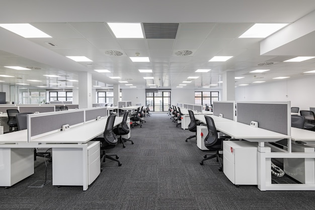 Modern corporate open office in minimalist modern design in whites and greys empty office workstations