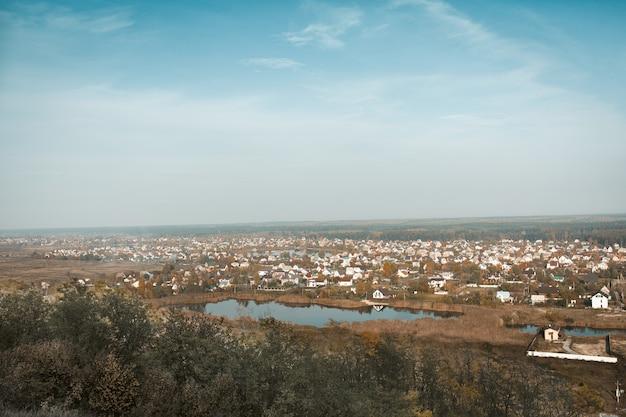 湖畔のモダンなコテージタウンまたはアーバンタイプの村。青い空を背景の農村のパノラマ風景。山から撮影。ハイアングル