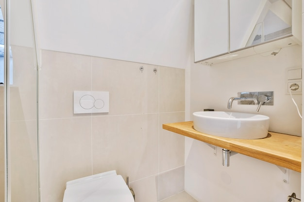 Modern countertop basin with wall faucet under mirror cabinet in toilet room with light tiles