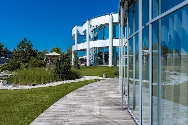 화창한 여름날 파티오가 있는 현대적인 시골 맨션과 조경된 녹색 정원