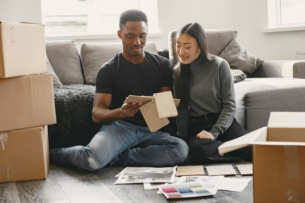 현대 부부는 가구 색상을 선택하고 있습니다. 그들의 새로운 가정에서 바닥에 앉아 귀여운 커플.