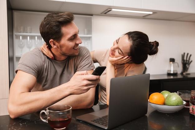 Современная пара мужчина и женщина, используя ноутбук со смартфоном, сидя на кухне