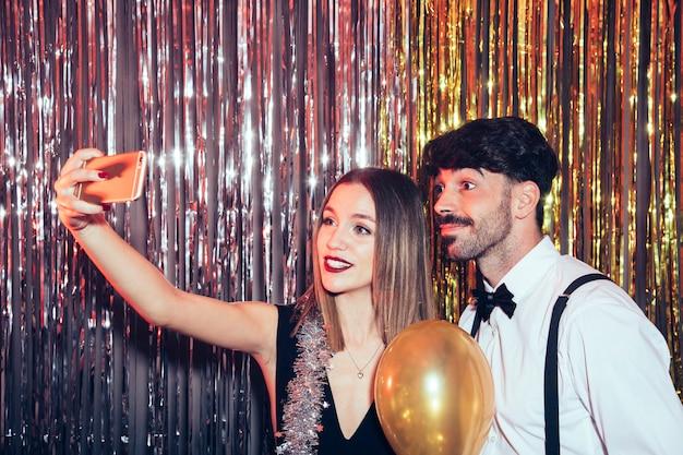 Coppia moderna che prende selfie su partiti di nuovi anni