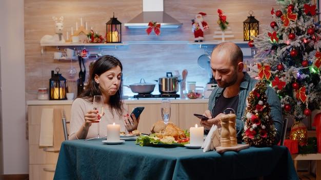 Modern couple using smartphones enjoying festive dinner