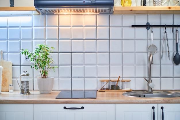 Современная уютная кухня-лофт с белой плиткой на стенах