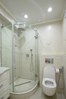 トイレとウォークインシャワーキャビン付きのモダンで居心地の良い白いバスルーム