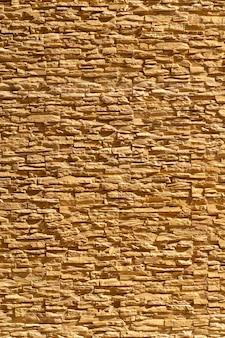 モダンなひびの入った茶色のオレンジ色のレンガは、背景の屋外フィールドで豪華な古典的な壁に配置されています。