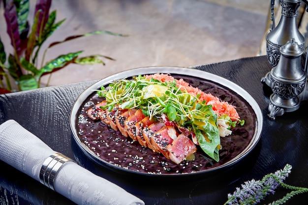 Современная кухня. редкий ростбиф с зелеными листьями салата и грейпфрутом. теплый салат на обед. здоровая пища. запеченное мясо. закройте горизонтальный. копировать пространство