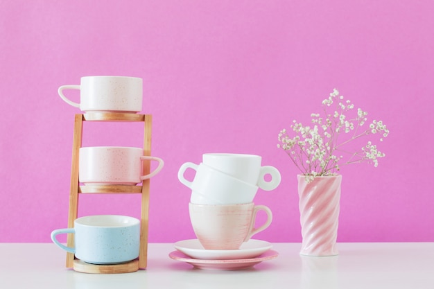 Modern cups on white table on background pink wall