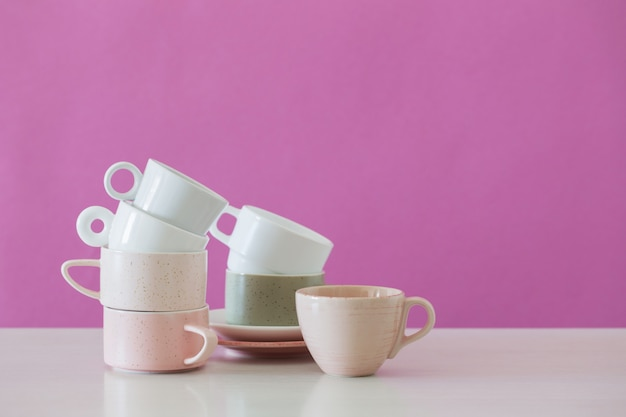 Modern cups on white table on pink wall