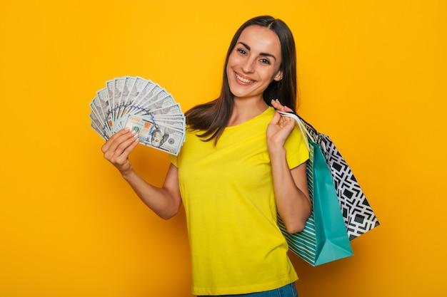 쇼핑백과 그녀의 손에 달러 현대 귀여운 웃는 젊은 여자는 노란색 벽 위에 포즈