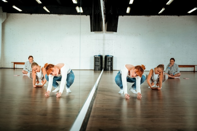 Modern dance elements. red-haired ballet teacher wearing blue jeans showing movements to her students