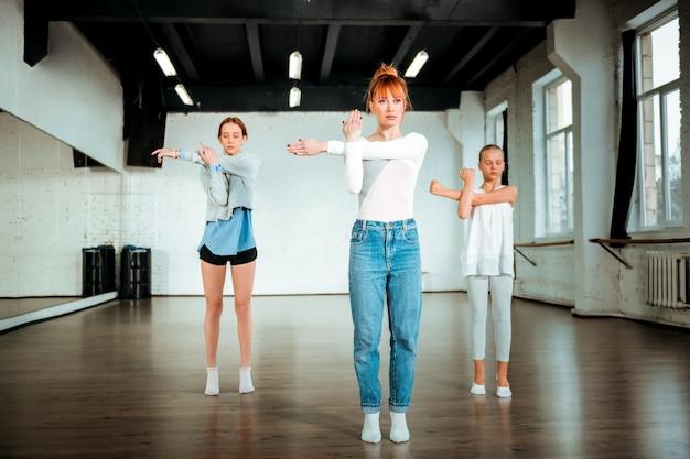 モダンダンスのレッスン。彼女の学生に動きを見せながら真剣に見える赤い髪のプロのモダンダンスの先生