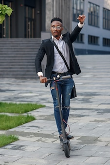 Современный темнокожий деловой человек катается на электросамокате после окончания рабочего дня в офисе.