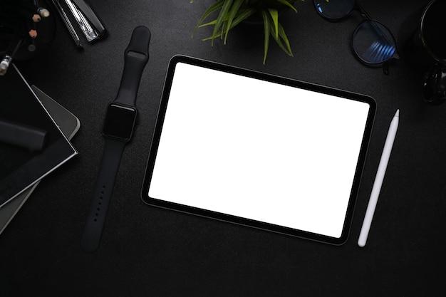 검은 가죽에 디지털 태블릿, 스마트 시계, 스타일러스 펜 및 노트북이 있는 현대적인 어두운 작업장.