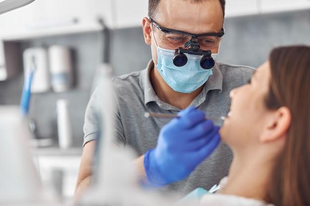 現代の歯科手術、患者に取り組んでいる女性医師の顔。歯科医院での患者への歯科インプラント手術。