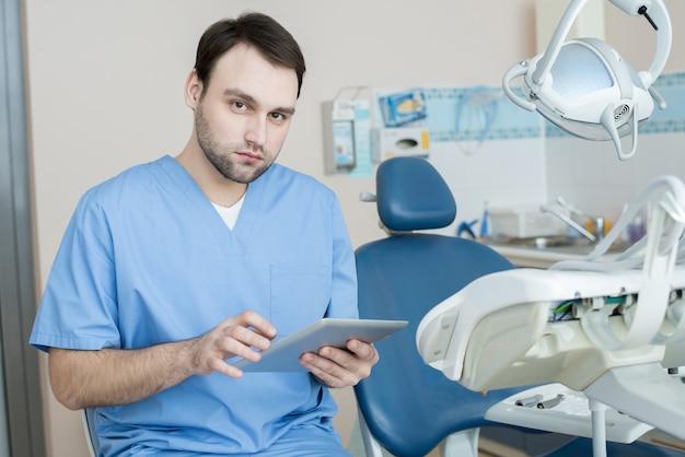 Современный стоматолог позирует в офисе