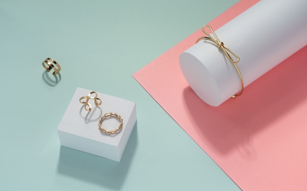 Modern design golden bracelet and rings on pastel color