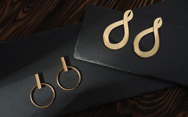 Серьги пар современного дизайна золотые на черных плитах на деревянном столе. пара сережек в форме бесконечности на плитах из черного камня