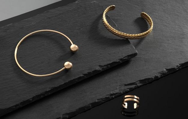 Золотые наручные манжеты и кольцо современного дизайна на темных каменных пластинах на черном фоне