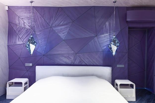 幾何学模様と美しいランプが付いた紫色の壁のある寝室のモダンなデザイン。