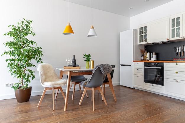 Современный дизайн интерьера столовой, кухни, белая мебель, лампы над деревянным столом, стулья, овечья шкура, дерево, ваза, винная бутылка, бокалы, концепция ипотеки, обложка журнала, горизонтальная