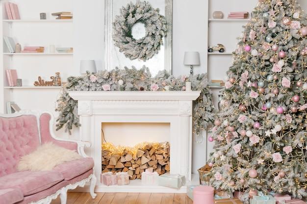 Современный дизайн комнаты с камином в светлых тонах украшен елкой и элементами декора, новогодними украшениями, зимними праздниками, елкой и подарками.