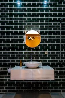 Современный дизайн умывальника с круглым зеркалом на черно-белой глянцевой плитке.