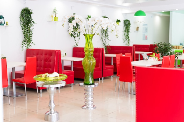 Modern design restaurant interior in white and red colors with plants