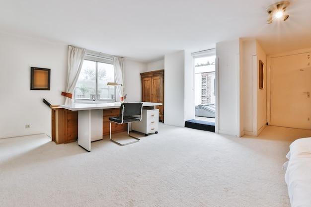 Современный стол и стул в просторном домашнем офисе с белыми стенами в светлом доме