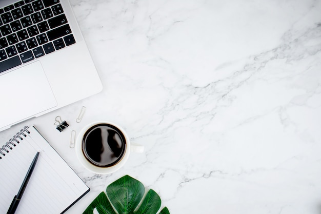 Modern desk with laptop computer, americano coffee and leaves. top view with copy space.