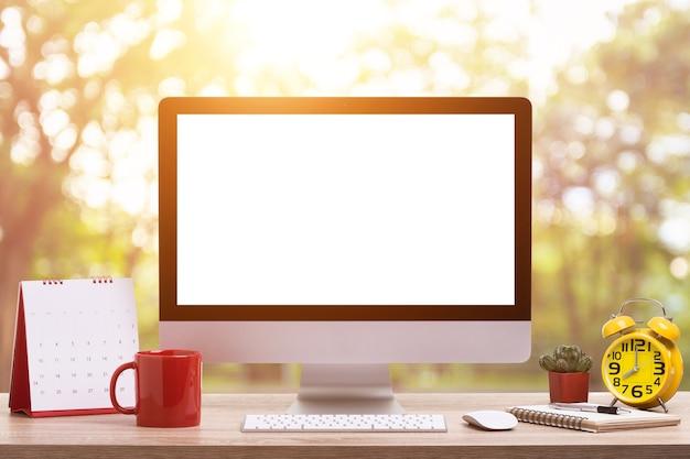 現代のデスクトップコンピュータ、コーヒーカップ、目覚まし時計、ノートブック、カレンダー