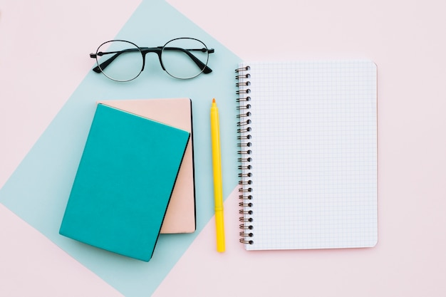 파스텔 색상 배경에 안경 및 책과 노트북 현대 데스크탑