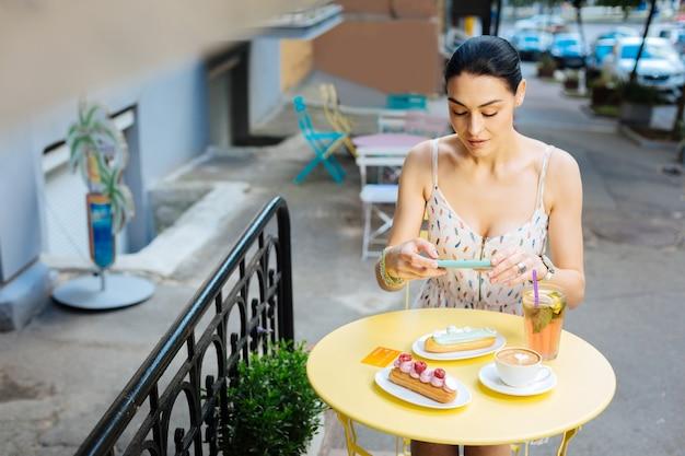 最新のデバイス。ストリートカフェの屋外のテーブルに座って、おいしいエクレアの写真を撮る美しい穏やかな女性