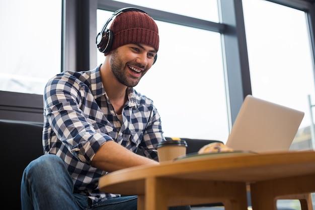 최신 장치. 쾌활한 긍정적 인 젊은이 미소하고 카페에서 작업하는 동안 노트북 화면을보고