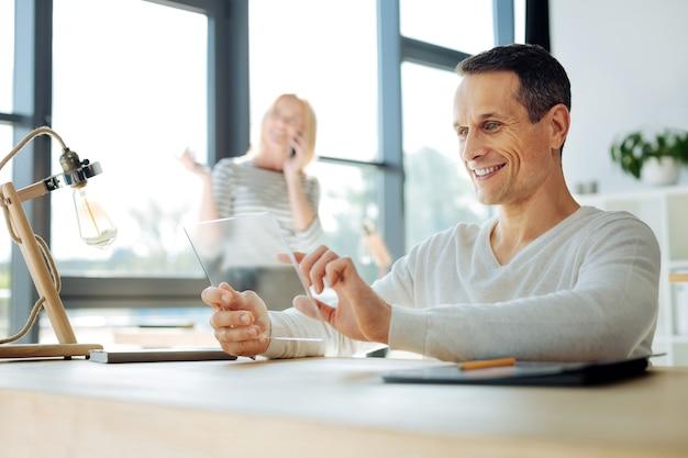 最新のデバイス。タブレットを持って、彼のオフィスのテーブルに座っている間それを使用して喜んでハンサムな格好良い男