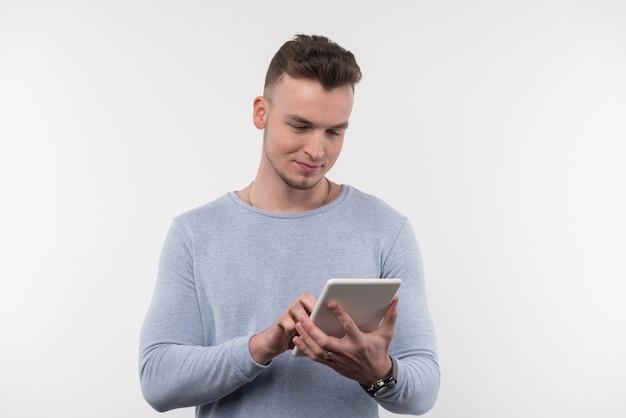 最新のデバイス。白い背景に立っている間タブレット画面を見て喜んでいい男