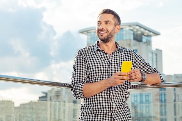最新のデバイス。建物からの眺めを楽しみながら彼の新しいスマートフォンを持って幸せな素敵な男