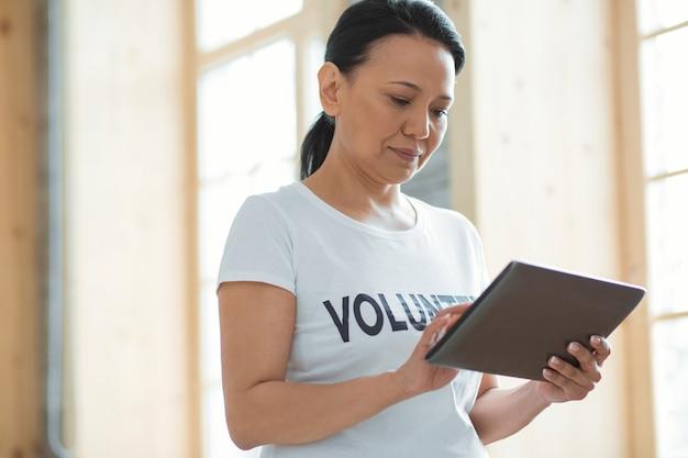 최신 장치. 흐린 배경에 서서 내려다 보면서 태블릿을 들고 즐거운 진지한 여성 자원 봉사자의 낮은 각도