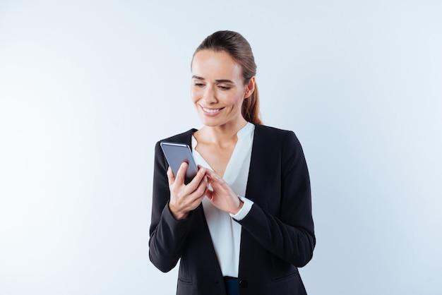 Современное устройство. позитивная счастливая веселая женщина смотрит на экран своего смартфона и улыбается, стоя на синем фоне