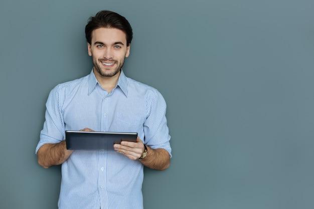 최신 장치. 긍정적 인 좋은 매력적인 남자 태블릿을 들고 그것을 사용하는 동안 웃고