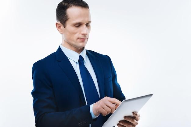 最新のデバイス。タブレットを持って仕事をしながらそれを使用して真面目な素敵なハンサムなビジネスマン