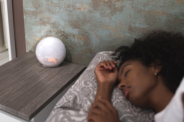 Modern digital alarm clock counting down time to awakening on bedside table