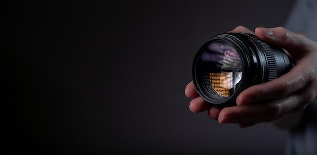 Современная цифровая камера объектива 85 мм в руке на темно-черном сером черном фоне с копией пространства для текста.