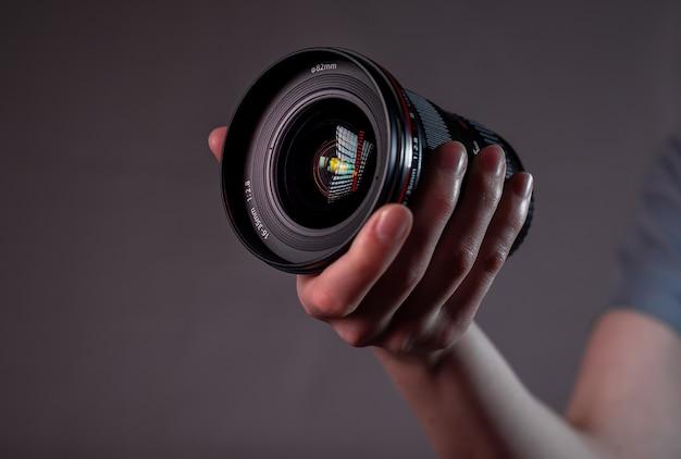 Modern digital camera lens in hand close up over dark background.